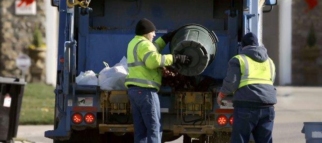 Solid waste division workers Travis Lindquist, left, and Derrick Jackson empty containers into the back of a trash truck as they make their rounds Thursday on Thorn Tree Court in west Lawrence. Recommendations are being made by the city's Sustainability Advisory Board to charge residents based on the amount of trash they throw away.