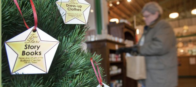 A shopper passes a Tree of Stars gift tree Tuesday at Waxman Candles, 609 Mass. The gift trees offer customers a way to donate items to needy families.