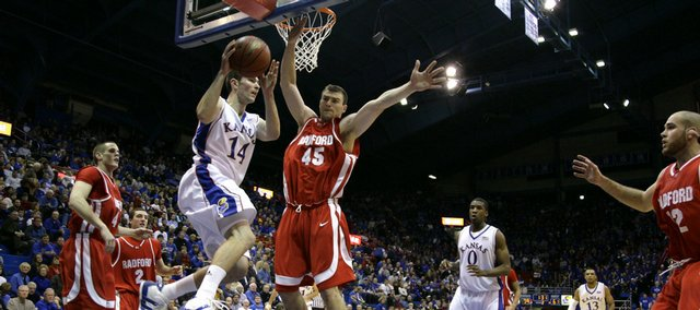 Kansas guard Tyrel Reed looks to pass out to the wing as he moves past Radford center Artsiom Parakhouski during the second half, Wednesday, Dec. 9, 2009 at Allen Fieldhouse.
