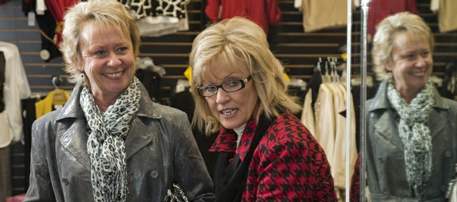 Judy Bronis tries on a gray European jacket selected by Cheryl Eckles.