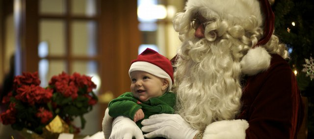 Five-month-old Langdon Smart, Lawrence, smiles for a photo on Santa's lap at Douglas County Bank on Saturday, Dec. 12, 2009.