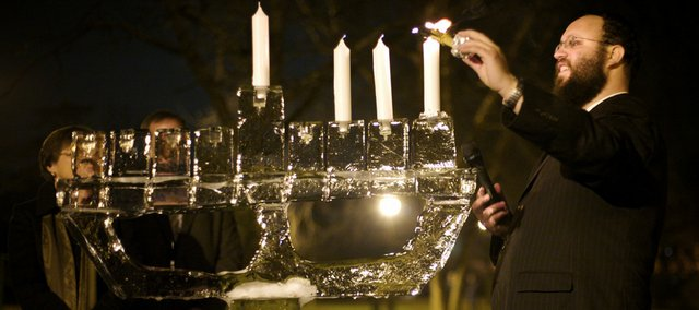 "Rabbi Zalman Tiechtel, executive director of the Chabad Center for Jewish Life, lights an ""Ice Menorah"" during Hanukkah in 2009."