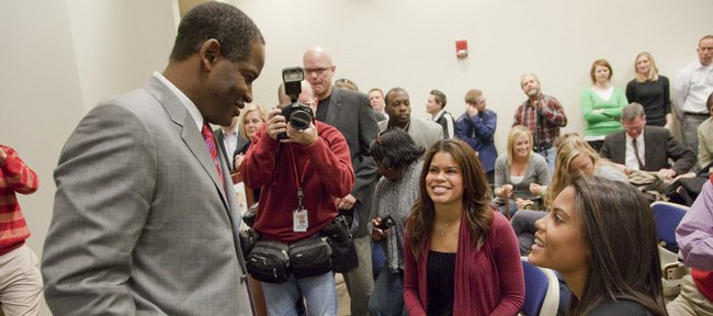 Turner Gill greets daughters Jordan, center, and Margaux, right, after Gill was introduced as KUs football coach during a news conference on Dec. 14, 2009.