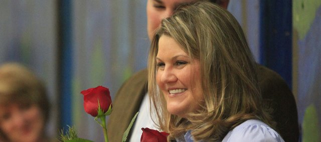 Special education teacher Mary Chamberlin is presented roses by her husband, Ryan Chamberlin, during a school assembly Thursday in which Chamberlin was awarded the $5,000 Dedication to Education Award by Pickney School officials and representatives of The Bobs, a group of anonymous donors who created the award.