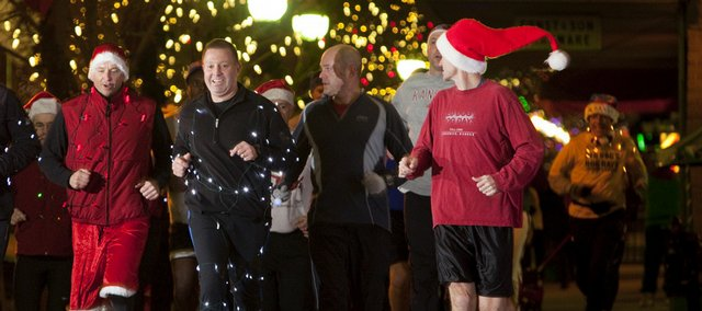 Donning holiday attire and lights, runners leading the pack make their way Thursday down the 800 block of Massachusetts Street during the Jingle Bell Run. Throughout the run, many participants spread holiday spirit by wishing glad tidings to passersby.