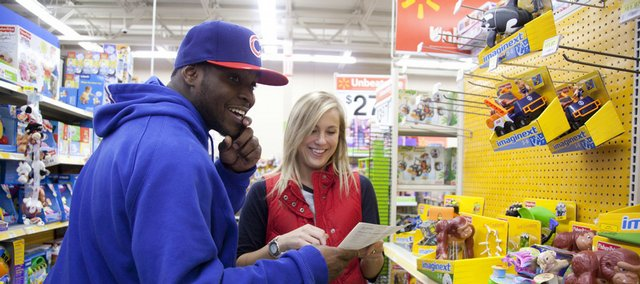 Kansas senior guard Sherron Collins, left, jokes with team manager Lacey Breech as the two shop for area families. Members of the KU basketball team shopped for 17 area families in need on Thursday at the south Lawrence Walmart.