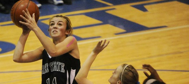 Free State's Lynn Robinson shoots an easy two against Leavenworth defenders Amanda Parks and Burgandie Lewis (32).
