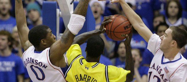 Kansas defenders Thomas Robinson and Brady Morningstar smother Michigan forward Manny Harris during the first half, Saturday, Dec. 18, 2009 at Allen Fieldhouse.