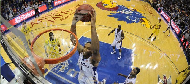 Kansas forward Xavier Henry soars in for a dunk over the Michigan defense during the second half, Saturday, Dec. 18, 2009 at Allen Fieldhouse.