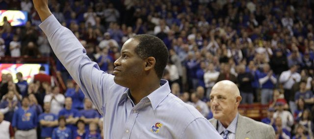 Kansas head football coach Turner Gill greets the Allen Fieldhouse crowd as he is introduced by athletic director Lew Perkins at halftime, Saturday, Dec. 18, 2009 at Allen Fieldhouse.