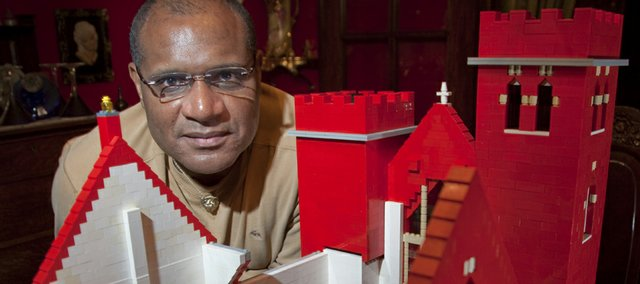 George Rennels shows off the inside detail of his giant Lego model of St. Luke's AME Church with congregation and pews.