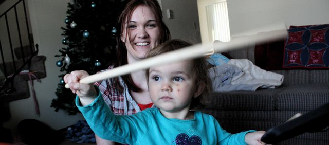 Reneé Mellenbruch, 19, of Lawrence plays Rock Band with her daughter Haylee. Mellenbruch juggles overnight work shifts and raising Haylee with help from day care and her mother.