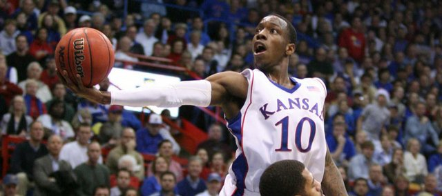 Kansas guard Tyshawn Taylor soars in for a bucket around California forward Jamal Boykin during the first half, Tuesday, Dec. 22, 2009 at Allen Fieldhouse.