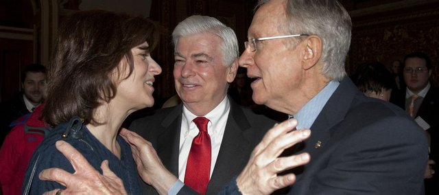 Victoria Kennedy, widow of Sen. Ted Kennedy, hugs Senate Majority Leader Harry Reid, of Nevada, Thursday, Dec. 24, on Capitol Hill in Washington, as Sen. Banking Committee Chairman Sen. Christopher Dodd, D-Conn., looks on at center, after the Senate passed the health care reform bill.