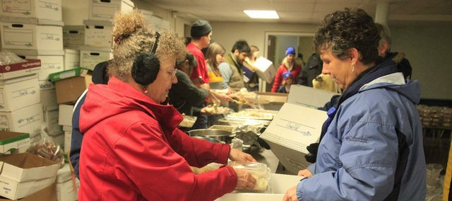 Volunteers Joleen Bechtel, left, and Jane Garvin help box up meals Friday at First United Methodist Church, 946 Vt. More than 600 such meals were to be delivered to area residents for Christmas.