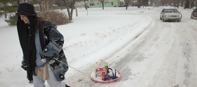 Kerry Townsend was resourceful in her quest to run to the grocery store for herself and a few neighbors. Using a saucer sled and rope to pull her groceries, she easily made her way along Connecticut Street near 15th Street Saturday, Dec. 26, 2009.
