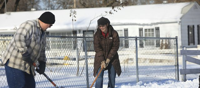 Kelly Jones, right, and others with the Douglas County Senior Services' Safe Seniors Walkway program volunteer to help Lawrence residents who cannot shovel their sidewalks after snowstorms. As Jones was working in the 1300 block of East 19th Street, neighbor Jerry Elliott, left, came to help.
