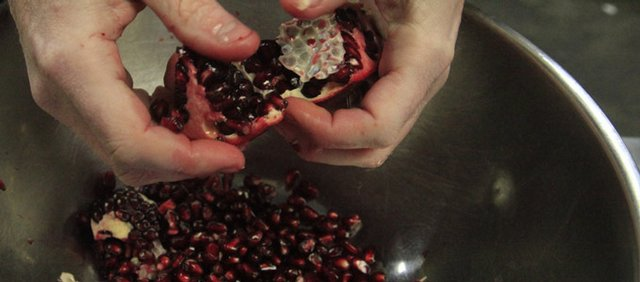 Ken Baker, chef and proprietor of Pachamama's, seeds a pomegranate.