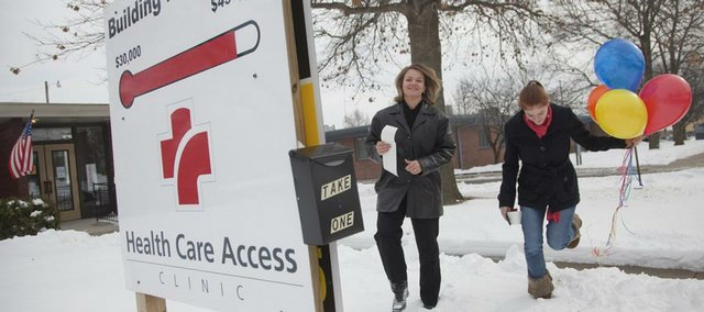 Nikki King, Health Care Access executive director, left, and Shasta Zielke, executive assistant and wellness coordinator, head to post the clinic's final fundraising tally in December. The clinic raised $453,000 to move to a larger location at 330 Maine, across the street from LMH's emergency department. It officially opened in the new location in February.
