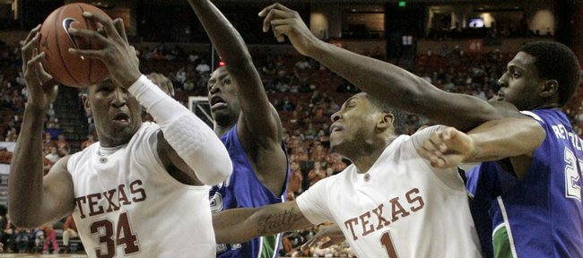 Texas center Dexter Pittman, left, attempts to elude Texas A&M-Corpus Christi defenders Horace Bond, second from left, and Justin Reynolds. Texas forward Gary Johnson (1) tries to box out the defense. The Longhorns squeaked by Corpus Christi, 76-70, on Saturday in Austin, Texas.