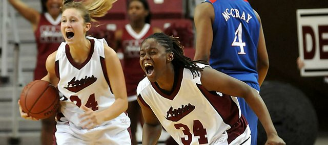 New Mexico State's Madison Spence (24) and Crystal Boyd (34) celebrate their victory over Kansas University as KU's Danielle McCray heads back to the bench. The Aggies beat KU, 61-60, Sunday in Las Cruces, N.M.
