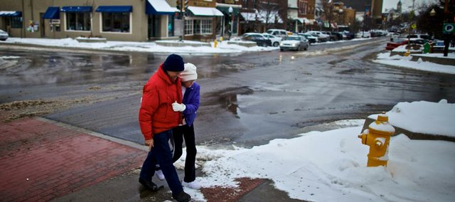 Tom Goetz helps his mother, Moesy Goetz, both of Lawrence, cross a slushy Massachusetts Street near Eighth Street on Sunday.