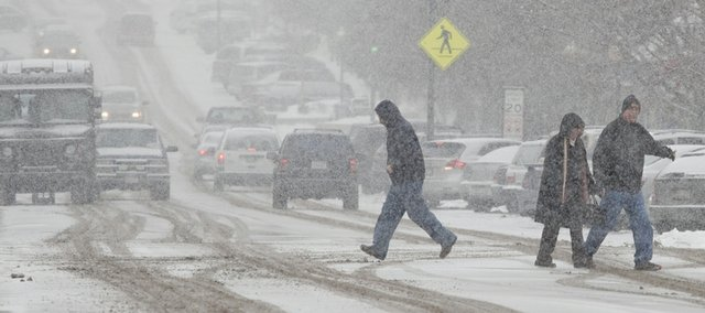 Pedestrians downtown make their way through an expected snowfall that began around noon Wednesday.