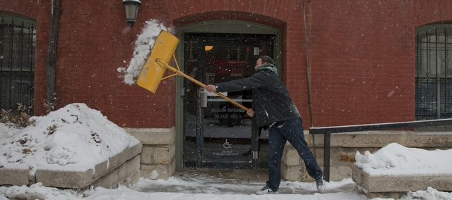 Spencer Mann throws snow that he was shoveling around the Watkins Community Museum as snow began to fall in the Lawrence area just after noon Wednesday, Jan. 6. The Colorado State freshman is working on his community service project before returning to college.