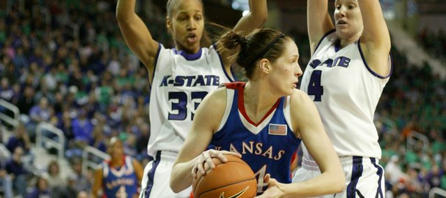 Kansas center Krysten Boogaard (14) tries to score behind Kansas State defenders Jalana Childs (33) and Ashley Sweat (4).
