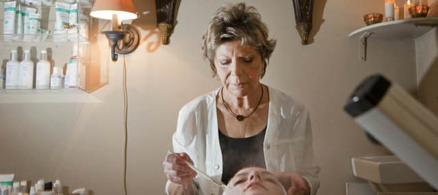 Joie Alkazian, of Avanti Salon, 1540 Wakarusa Drive, gives a facial to a client. She says a light facial peel with glycolic acid will help remove dead, dry skin.