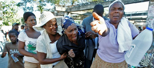 A group of women react Thursday as the daughter of the woman, at center, is still missing after the earthquake in Port-au-Prince.