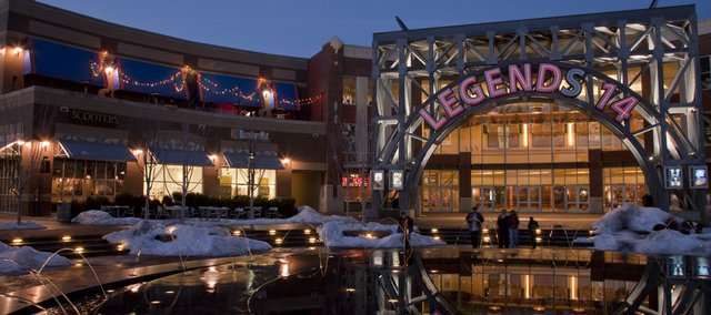 The Legends 14 movie theater sign is reflected in the fountain pool that is a centerpiece fixture in the shopping complex in Kansas City, Kan. Sales tax numbers show that the Legends and other shopping areas might be drawing people away from spending in Lawrence.