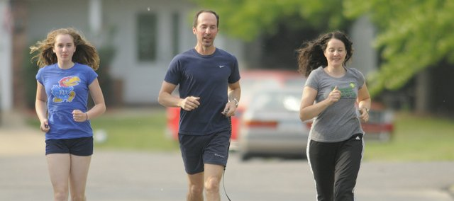 "Stephen Ilardi, center, an associate professor at Kansas University, jogs with his daughter, Abby, 12, left, and wife, Maria. Ilardi has written a book, ""The Depression Cure,"" which recommends exercise as one component of the treatment."