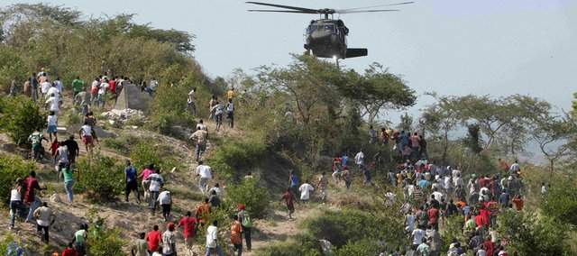 People run toward a U.S. helicopter as it makes a water drop Saturday near a country club used as a forward operating base for the U.S. 82nd Airborne Division in Port-au-Prince, Haiti. Relief groups and officials are focused on moving aid flowing into Haiti to survivors of the powerful earthquake that hit the country on Tuesday.