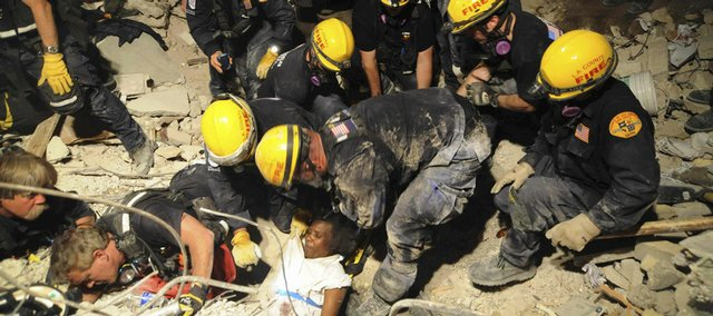 Members of the Los Angeles County Fire Department's Search and Rescue Team rescue a Haitian woman from a collapsed building Sunday in downtown Port-au-Prince, Haiti.