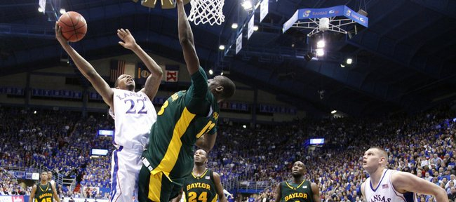 Kansas forward Marcus Morris hangs for a shot around Baylor center Ekpe Udoh during the second half, Wednesday, Jan. 20, 2010 at Allen Fieldhouse. At right is Kansas Center Cole Aldrich.