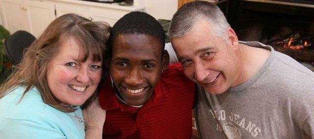 Wanda and Scott Miller hug their new son, Junior Oranvil Miller, in this Jan. 18 photo in their Hesston home. They adopted him from Haiti after more than six years of waiting.