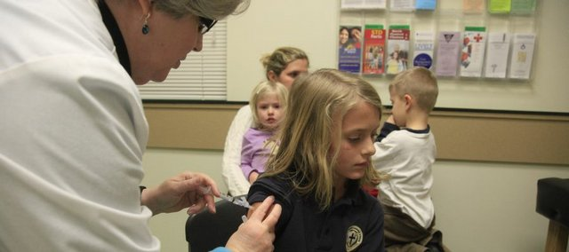 Carole Rehder, a retired nurse, gives Leslie Ostronic, 9, her second dose of the H1N1 flu vaccine in January at the Lawrence-Douglas County Health Department clinic. In the background is Leslie's mother, Laurie, who is holding siblings Brecken, 4, and Dallas, 5. The children all received an immunization.