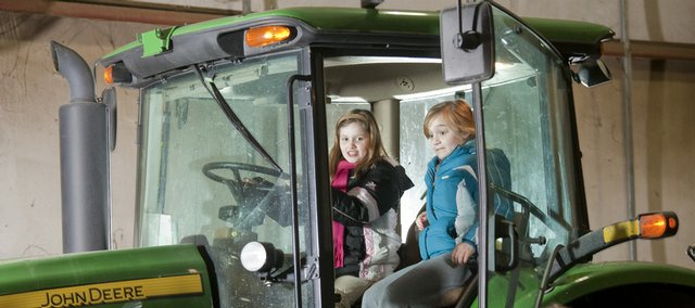 Reagan Sullivan, left, and Emma Perez, both fourth-graders at Langston Hughes School, experience the view from the cab of a modern tractor Thursday during a Slice of Ag event at the Douglas County 4-H Fairgrounds, 21st and Harper streets. The event, sponsored by K-State Research and Extension, provided fourth-graders from area schools a close look at farm life, including viewing hogs, beef and dairy cattle.