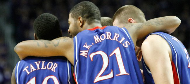 Kansas teammates Tyshawn Taylor, Markieff Morris and Cole Aldrich pull together during a timeout in overtime against Kansas State, Saturday, Jan. 30, 2010 at Bramlage Coliseum.