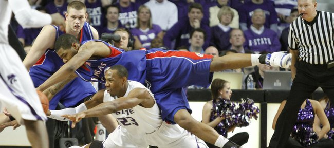 Kansas forward Marcus Morris is called for a foul as he dives for a loose ball over Kansas State forward Dominique Sutton during the second half Saturday, Jan. 30, 2010 at Bramlage Coliseum. At left is Kansas center Cole Aldrich.