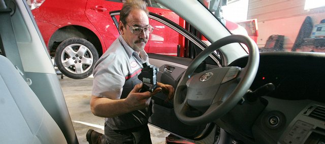 Steve Newton, a Toyota Master Diagnostic Service Technician, installs a shim, a piece of steel about the size of a postage stamp, into the gas pedal assembly of a Toyota Avalon in Dubuque, Iowa.