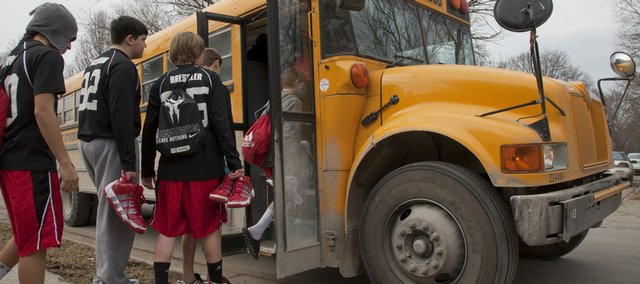The Central Junior High boys' eighth-grade basketball team boards a bus Wednesday to travel for an away game. Lawrence school officials are looking for ways to further trim the district's budget, perhaps by eliminating or cutting costs in various after-school music, fine arts and athletics programs, among other possibilities.