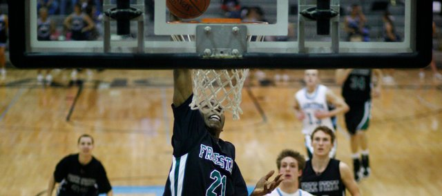 Free State's Eric Watson (21) throws down a jam in the second half. The Firebirds defeated Shawnee Mission East, 63-49, on Friday in Prairie Village.