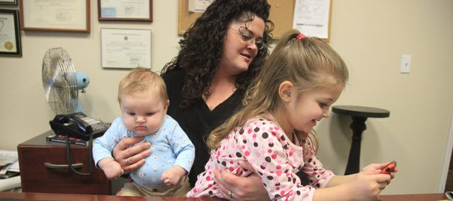 Beth Barnett, Lawrence, and daughters Isabella, 3 months, and Gabrielle, 3, have a moment together at her workplace. Barnett uses various vocalization techniques to help her young children develop language skills.