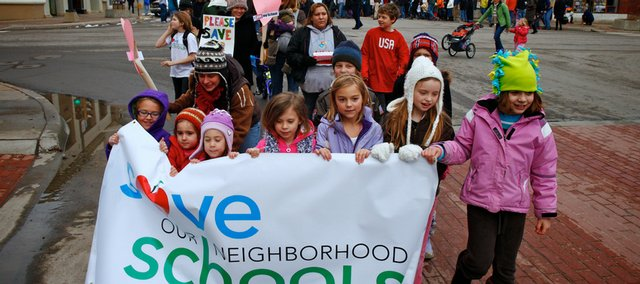 A group of girls leads a march, organized by Save Our Neighborhood Schools, on Saturday from Liberty Hall, 644 Mass., down Massachusetts Street. Hundreds of students and parents turned out to protest the Lawrence school board's consideration of closing some elementary schools to close a budget shortfall.