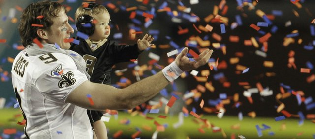 New Orleans quarterback Drew Brees holds his son Baylen after the Super Bowl. Brees was named MVP after the Saints' 31-17 victory Sunday over the Colts in Miami.