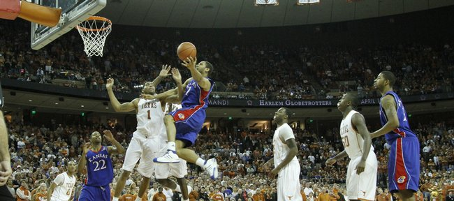 Kansas forward Xavier Henry draws a foul as he flies past Texas forward Gary Johnson during the second half, Monday, Feb. 8, 2010 at the Frank Erwin Center in Austin.