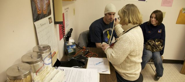 Louis Shannon, left,  of Lawrence, gets his temperature and other vitals taken by Jeri Safarik, a registered nurse, on Feb. 9, 2010, at Health Care Access clinic, which serves low-income, uninsured Douglas County residents. Jamie Kessler is seated to the right.