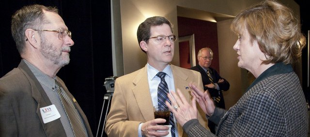 U.S. Sen. Sam Brownback, R-Kan., center, visits with Kansas Rep. Tom Sloan, R-Lawrence, left, and Cheryl Seiwald, a member of the board of directors of the Lawrence Technology Association at the association's annual meeting Thursday at Maceli's, 1031 N.H.